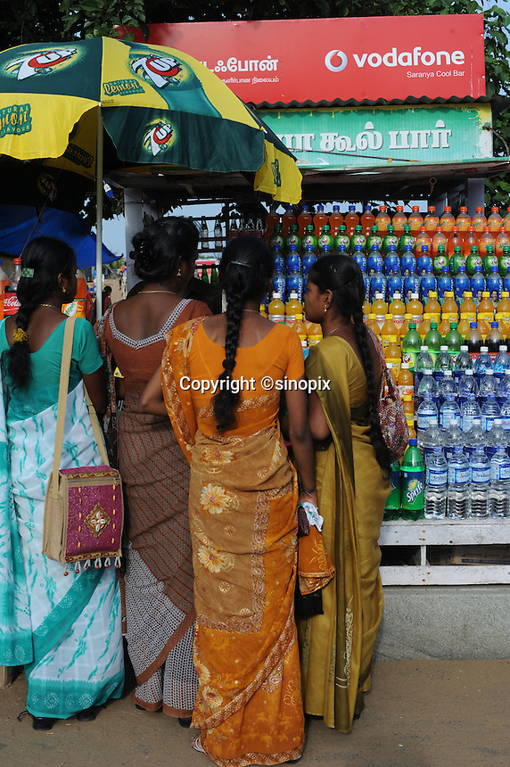 Ladies buy drinks from outside drink vender in Madras, India