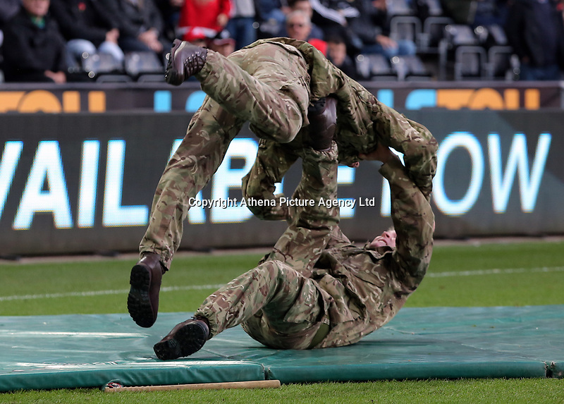 Members of the armed forces perform for the crowd during the Premier League match between Swansea City and Brighton and Hove Albion at The Liberty Stadium, Swansea, Wales, UK. Saturday 04 November 2017
