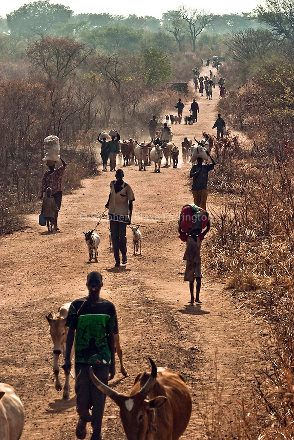 Africa, Sudan, Magwi County, Mugale/Nimule Road, Caught In Between, Northern Uganda/Southern Sudan - Villagers from Mugale flee their village. The Lord's Resistance Army ambushed Mugale, injuring a woman and killing a man. Since the attack the 15,000 inhabitants of Mugale have been making an exodus out of the village towards nearby Nimule. The war in the region began in 1986 between the Lord's Resistance Army and the Ugandan People's Defense Forces (UPDF). The LRA has reigned terror and carnage on Northern Uganda and Southern Sudan ever since. The ongoing conflict has significantly damaged the region and has left an ongoing burden on the local population. December 2005 © Stephen Blake Farrington