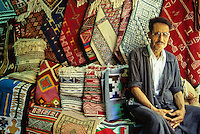 Tunisia.  Tunis Medina.  Gassam, a Seller of Rugs and Textiles.