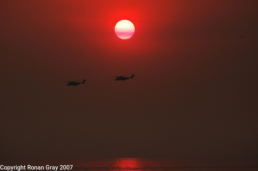 Two military helicopters are silhouetted against a smoke filled sky at sunset off the coastal town of Del Mar, San Diego California where wild brush fires raged for a third day, Tuesday, October 23, 2007.  Many reports credited the assistance of several military helicopters in helping to contain one of the many fires burning in the area today.