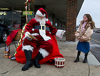 Santa Claus, portrayed by Santa Clarence, a member of the Amalgamated Order of Bearded Santas, talks with a girl outside a shipping store where he greeted young and old to hear their Christmas wishes.
