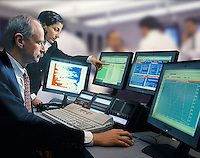 &#x9;Business colleagues review data on computer monitors.<br />