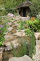 HESCO garden, Leeds, RHS Chelsea Flower Show 2009. Plants include: Primula  beesiana, Primula florindae, Camassia cusickii (wild blue hyacinth), Rhododendron 'Gibraltar'.