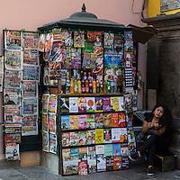 Peru, Lima.  Woman and Newsstand.