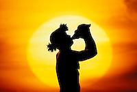 A massive sun silhouettes a conch blower.