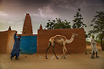 AGADEZ, NIGER — <br /> Tuareg camel traders walk past the Agadez Mosque. Originally built in 1515 this mosque was restored in 1844 and is a central landmark in this city. <br /> Agadez, is the largest city in central Niger with an estimated population of over 120,000 people. This city, comprised mainly of one-story mud structures, is situated on the southern outskirts of the Sahara desert and has been an important trade center for centuries. Tuareg and Berber tribes have traveled the many commercial routes that run through the desert for more than a thousand years. Today, this city has become one of the largest human smuggling and drug trafficking routes in West Africa. Thousands of migrants attempting to reach Europe are smuggled through the Sahara desert to Libya, Algeria and Morocco in their attempts to reach Italy and Spain.