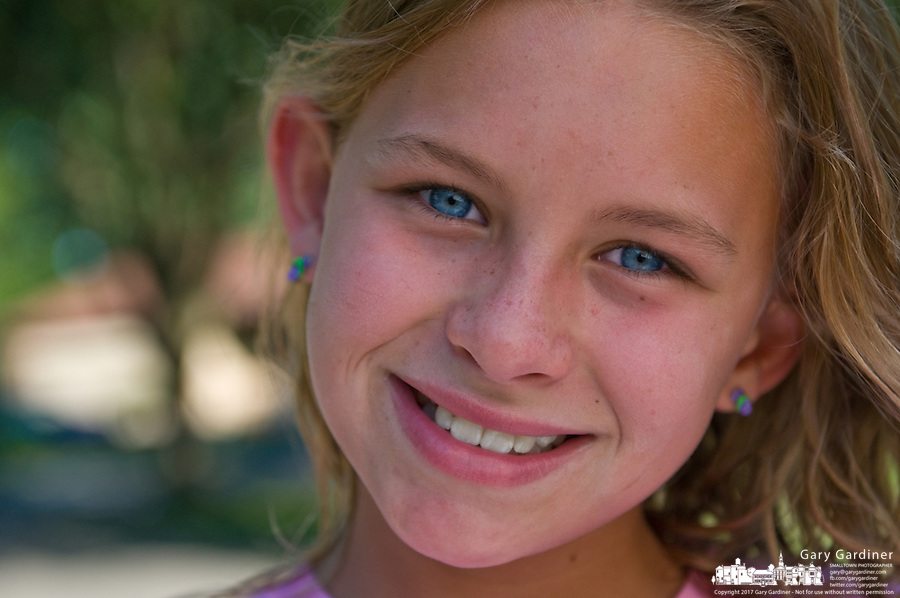 Young girl, 10-15, with blue eyes and blonde hair smiles