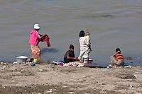 Myanmar, Burma. Bagan.  Ayeyarwady (Irrawaddy) River Scene.  Women Doing Laundry.