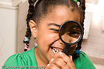 Education Preschool 4-5 year olds laughing girl holding magnifying glass up to her eye horizontal