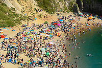 BNPS.co.uk (01202 558833)<br /> Pic: Graham Hunt/BNPS<br /> <br /> The beach is packed with sunbathers and visitors at Durdle Door in Dorset on an afternoon of scorching hot sunshine and clear blue skies as the heatwave continues.