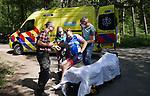 Foto: VidiPhoto<br /> <br /> MAARSBERGEN – Hulpdiensten hadden het zaterdag druk. Door de combinatie van aangenaam fiets- en motorweer waren de toeristische binnenwegen overvol. Dat zorgde voor tal van kleine ongevallen waarbij gewonden vielen, zoals hier op de Haarweg in Maarsbergen. Een wielrenner kwam ongelukkig ten val, waarbij zijn heup uit de kom schoot. Passerende fietsers en automobilisten lieten de man liggen. Alleen een groep motorrijders stopte -onder wie een brandweervrijwilliger- verleende eerste hulp, waarschuwde de ambulance en zorgde dat de racefiets van de man veilig werd gestald.