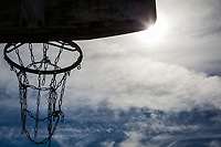 The view from behind the backboard of a neighborhood park's basketball hoop with its metal chain net.  The scene includes a cloud-painted sky and a sunburst at the backboard's corner.