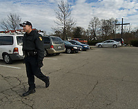 A police officer patrols a church parking lot to prevent people from placing election materials on car windshields the Sunday before the election.<br />