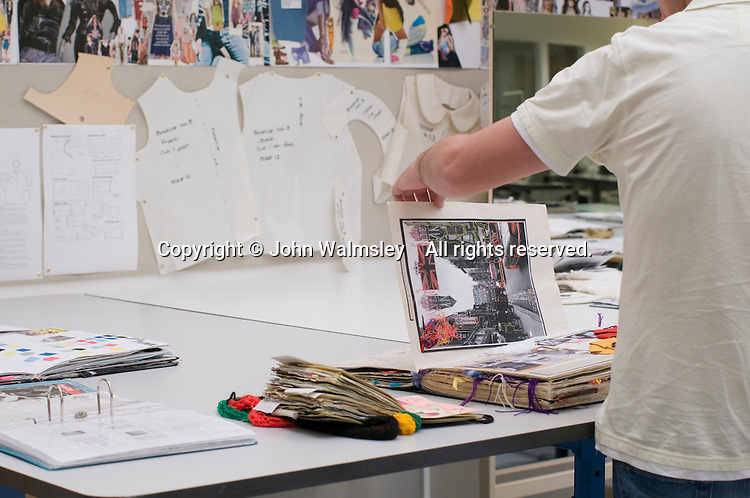 A father looking through display work, Open Day at Kingston College when prospective students and their parents look around.