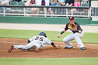 Gregory Lorenzo (25) of the Delmarva Shorebirds dives head first back towards first base as Danny Hayes (32) of the Kannapolis Intimidators waits for a pick-off throw at CMC-NorthEast Stadium on July 3, 2014 in Kannapolis, North Carolina.  The Shorebirds defeated the Intimidators 6-5. (Brian Westerholt/Four Seam Images)