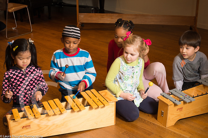 Education elementary school Grade 1 music activity boy and girl playing percussion instrument as classmates listen