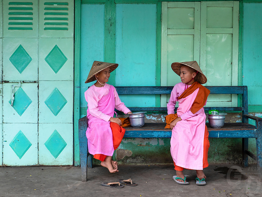 Novice Nuns waiting to collect their Alms in Sagaing at a colourful Building