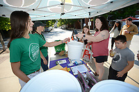 Taylor Gladwin (from left) and Heather Ellzey, both environmental educators for the city of Fayetteville, hand a food waste collection bucket and information Saturday, July 24, 2021, to Liz Greene of Fayetteville and her children Abram Greene, 6, and Amelia Greene, 11, at the Fayetteville Farmers' Market. The city is encouraging residents to drop off food waste to turn into compost. Residents can drop off food waste among five locations in the city or at the mobile trailer at the Farmers Market every second and fourth Saturday. Visit nwaonline.com/210725Daily/ for today's photo gallery.<br /> (NWA Democrat-Gazette/Andy Shupe)