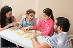 3 year old boy at home memory game with sister age 8 and parents