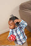 17 month old toddler boy holding ball and trying to comb own hair with large comb