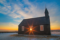 This is the Little Black Church at Búðir on the Snæfellsnes Peninsula, Iceland.  It is black since the wood is coated with pitch, just like a boat hull might be for weather proofing.  There are several of the black churches in Iceland.  We drove a couple hours north of Reykjavík to get here, through some of the most beautiful sunrise pinks we had ever seen.  We thought maybe all mornings were like that in Iceland.  This is not an early morning sunrise as it would be if this scene were in the USA.  In the winter, the sun does not get too much higher than shown in this photo.  As a result the sunrises and sunsets can last over an hour each.  Beautiful country for photographers.