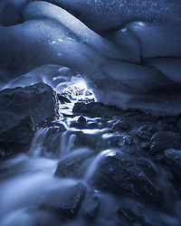A cave carved through a small glacier deep in Oregon's Three Sisters Wilderness.