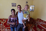 Feride Ramadan Mehmed (left) and her husband Mehmed hold their son Erdzhan, 3, in their house in the Maxsuda neighborhood of Varna, Bulgaria. They are Turkish-speaking Roma, and were violently driven out of one neighborhood by racist gangs. They took refuge in a United Methodist Church for a year before finding this small house to rent.
