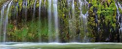 Water cascades down moss laden cliffs into the Sacramento River at a unique falls in Northern California.