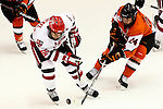Saint Lawrence University's Justin Bruckel (55) and Rochester Institute of Technology's Chris Haltigin (24) battle of for the puck during the first period. SLU and RIT are tied one goal a piece at Blue Cross Arena in Rochester, NY on October 15, 2011