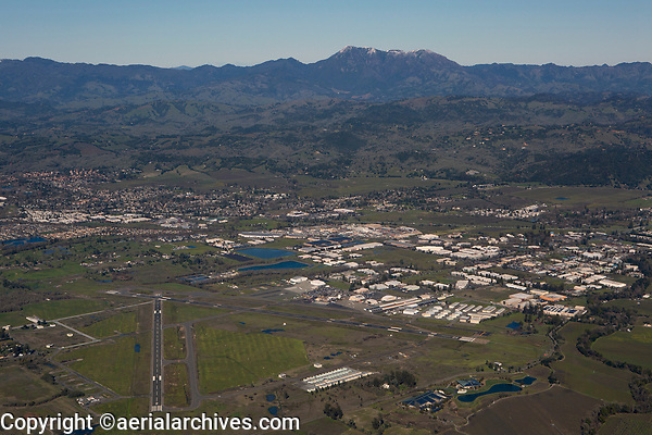aerial photograph of the Charles M. Schultz, Sonoma County Airport (STS), Santa Rosa, Sonoma County, California with a view down runway 2 toward Mount Saint Helena and the Mayacamas Mountains; the Airport Business Center in Windsor is immediately beyond the airport, as is highway 101 just past the business center; immediately beyond highway 101 are a number of hillside vineyards