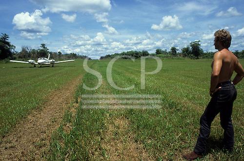 Pavuru Village, Brazil. Sting standing beside a grass airstrip with a small plane; Xingu, Nov 1990.