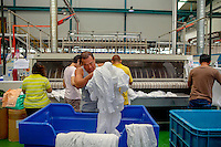 Workers in an industrial laundry that operates almost exclusively for the Marina Bay Sands resort hotel.
