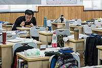 A student eats his lunch while sitting in his class room during a meal break at the prestigious  Shanghai High School in Shanghai, China on 27 February, 2014.  As one of the most demanding and exclusive high school in the country, Shanghai High School puts grueling study hours on its students, academic studies often last from 6:45 Am to as late as 9 PM.