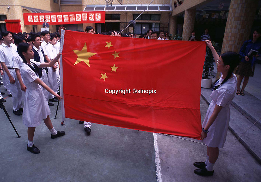 090597: HEUNG TO MIDDLE SCHOOL: HONG KONG<br /> <br /> Pupils in form 2B (14 years of age) read a pro-China newspapers first thing in the morning, each morning.  The school is one of a hand-full of schools in Hong Kong that openly show allegiance to the communist government in China.