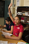 Education high school classroom scenes girl raising hand to ask question or supply answer