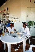 Kasama, Zambia. Two well-dressed women wearing hats sitting at a cafe table.