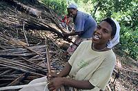 Women collecting leaves to make traditional roofing, Sulphur Bay Village, Ipekel Ipeukel, Tanna Island, Vanuatu.