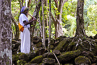 A tall man wearing white clothes and a headscarf plays a flute surrounded by huge boulders and trees at Limahuli Gardens, on Kauai's majestic north shore. One of the 5 National Tropical Botanical gardens in the US.