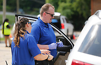 Melissa Snider (left), paramedic with Central EMS, and Levi Turner, emergency medical technician, prepare Tuesday, July 20, 2021, to give a driver a covid-19 vaccination shot during the weekly St. James Missionary Baptist Church Food Pantry at the Squire Jahagen Arts and Outreach Center located at 115 S. Willow Avenue in Fayetteville. St. James Missionary Baptist Church, Central EMS and the Arkansas Department of Health hosted a drive-up covid-19 vaccination clinic at the center during the food pantry distribution hours. Check out nwaonline.com/210721Daily/ and nwadg.com/photos for a photo gallery.(NWA Democrat-Gazette/David Gottschalk)