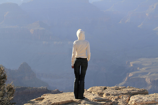 Young woman standing on the edge of the South Rim of Grand Canyon National Park, Arizona. . John offers private photo tours in Grand Canyon National Park and throughout Arizona, Utah and Colorado. Year-round.