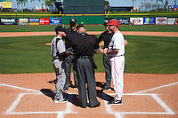 Ball State Cardinals head coach Rich Maloney (right) talks with Louisville Cardinals head coach Dan McDonnell (left) as umpires (L-R) Landon Davis, Ray Parrish, and Shane Livingsparger look on during the lineup exchange before a game on February 19, 2017 at Spectrum Field in Clearwater, Florida.  Louisville defeated Ball State 10-4.  (Mike Janes/Four Seam Images)