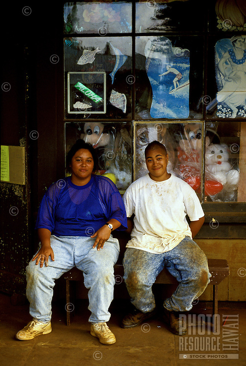 Two young female pineapple workers sit in front of an old mom and pop store in Lanai City, Lanai, Hawaii.