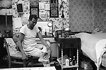 Asian Muslim 1980s UK immigrant man male in bed sitting room that he shares with his wife Blackburn Lancashire England. He is unwell. 1983