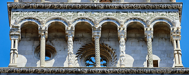 Close up of the Arcades columns & statues of St Michele of the 13th century Romanesque facade of the San Michele in Foro,  a Roman Catholic basilica church in Lucca, Tunscany, Italy