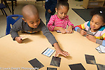 Preschool 3 year olds two girls and boy playing matching cards game taking turns