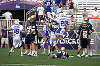 Steve Schoeffel (20), Max Quinzani (8) and teammates surround CJ Costabile (9) of Duke after he scored the game winning goal in overtime of the NCAA Men's Lacrosse Championship held at M&T Stadium in Baltimore, MD.  Duke defeated Notre Dame, 6-5, to win the title in overtime.
