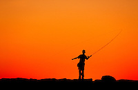 Boy fishing from a jetty at sunset, Menemsha, Martha's Vineyard