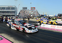 Sept. 22, 2012; Ennis, TX, USA: NHRA funny car driver Courtney Force (near lane) races alongside Ron Capps during qualifying for the Fall Nationals at the Texas Motorplex. Mandatory Credit: Mark J. Rebilas-US PRESSWIRE