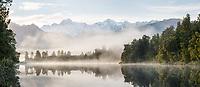 Southern Alps with Aoraki Mount Cook and Horokoau Mount Tasman reflecting in Lake Matheson at moody sunrise, Westland Tai Poutini National Park, UNESCO World Heritage Area, West Coast, New Zealand, NZ